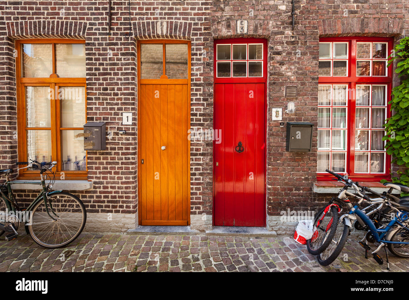 Doors of old houses and bicycles in european city. Bruges (Brugge), Belgium - Stock Image