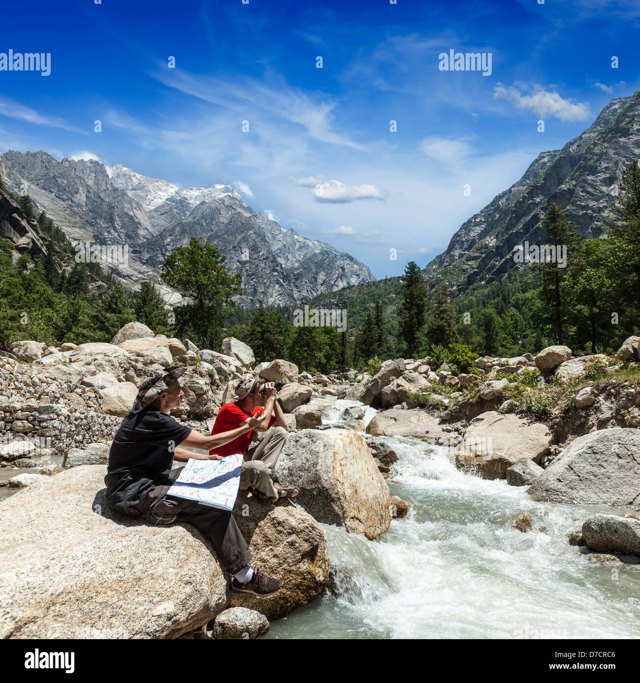 Hiker trekkers read a trekking map on trek in Himalayas mountains. Himachal Pradesh,India - Stock Image