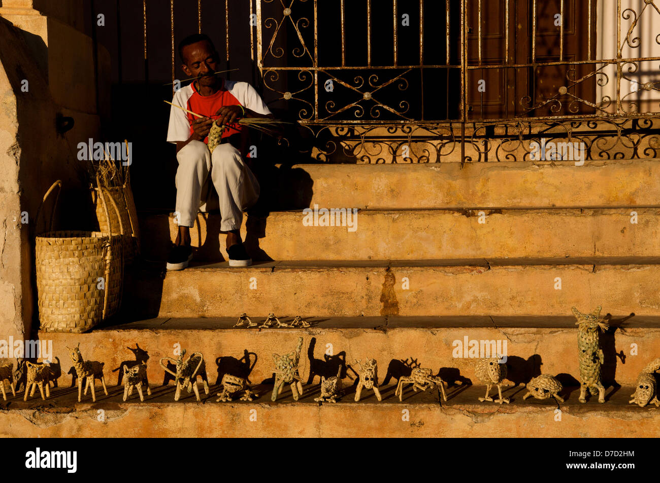 Cuban man making straw animals on steps, Trinidad, Sancti Spíritus province, Cuba. © Kraig Lieb - Stock Image