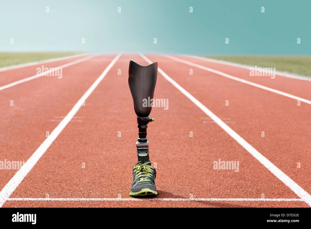 Athletic sports prosthesis of a disabled athlete stands on a tartan track - Stock Image