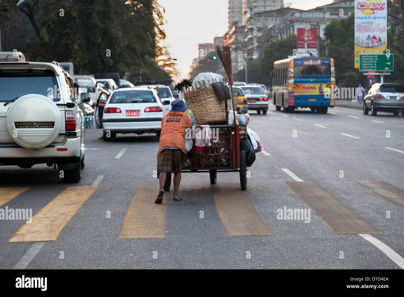 Garbage wagon braving the early evening traffic in Yangon, Myanmar - Stock Image