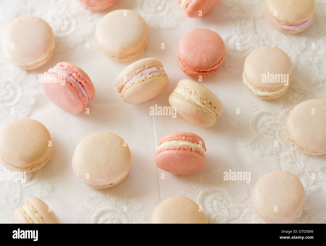 Assortment of French almond macarons on white wood, part of a series. - Stock Image