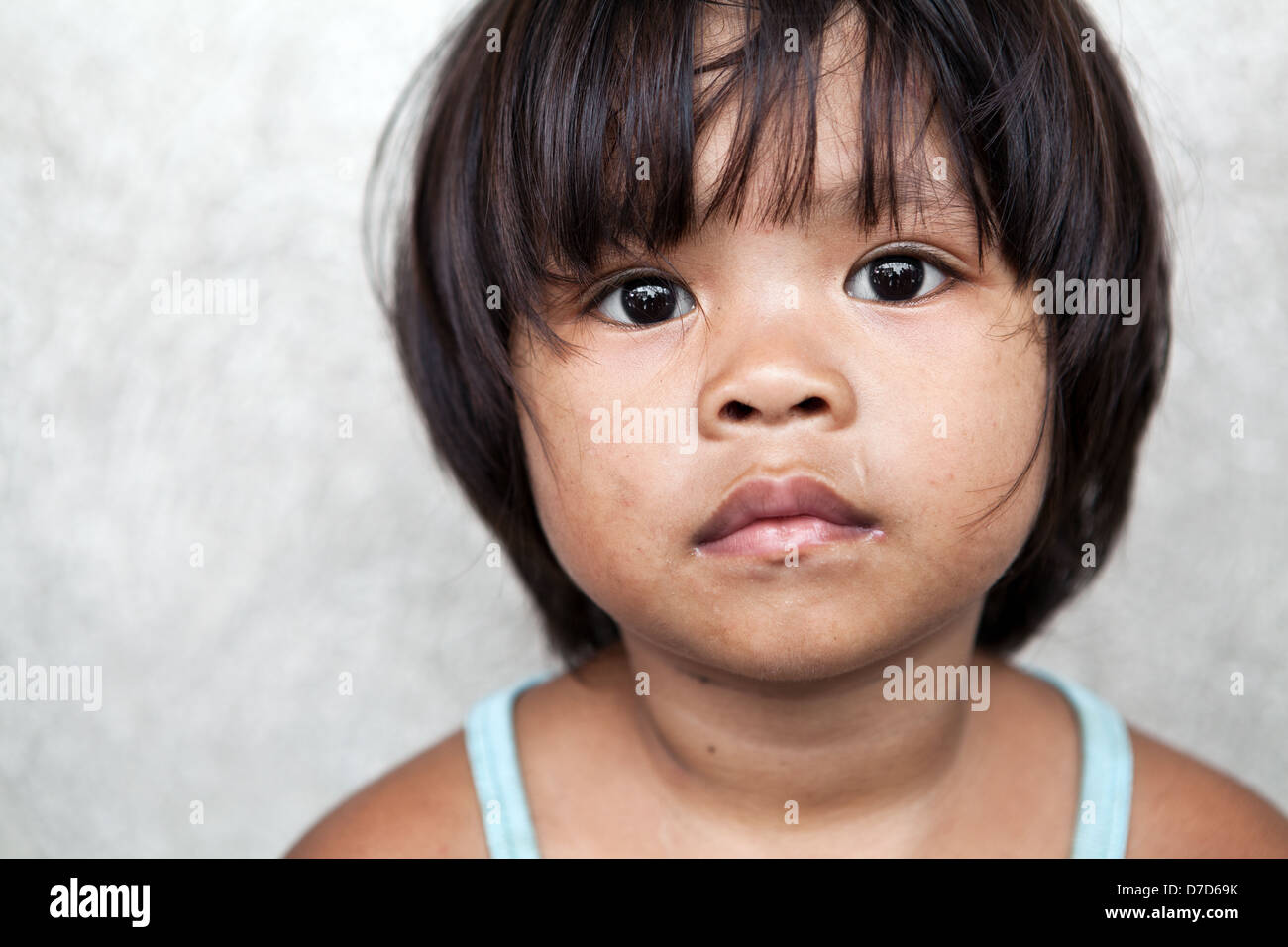 Young girl in the Philippines living in poverty against off-white wall - Stock Image