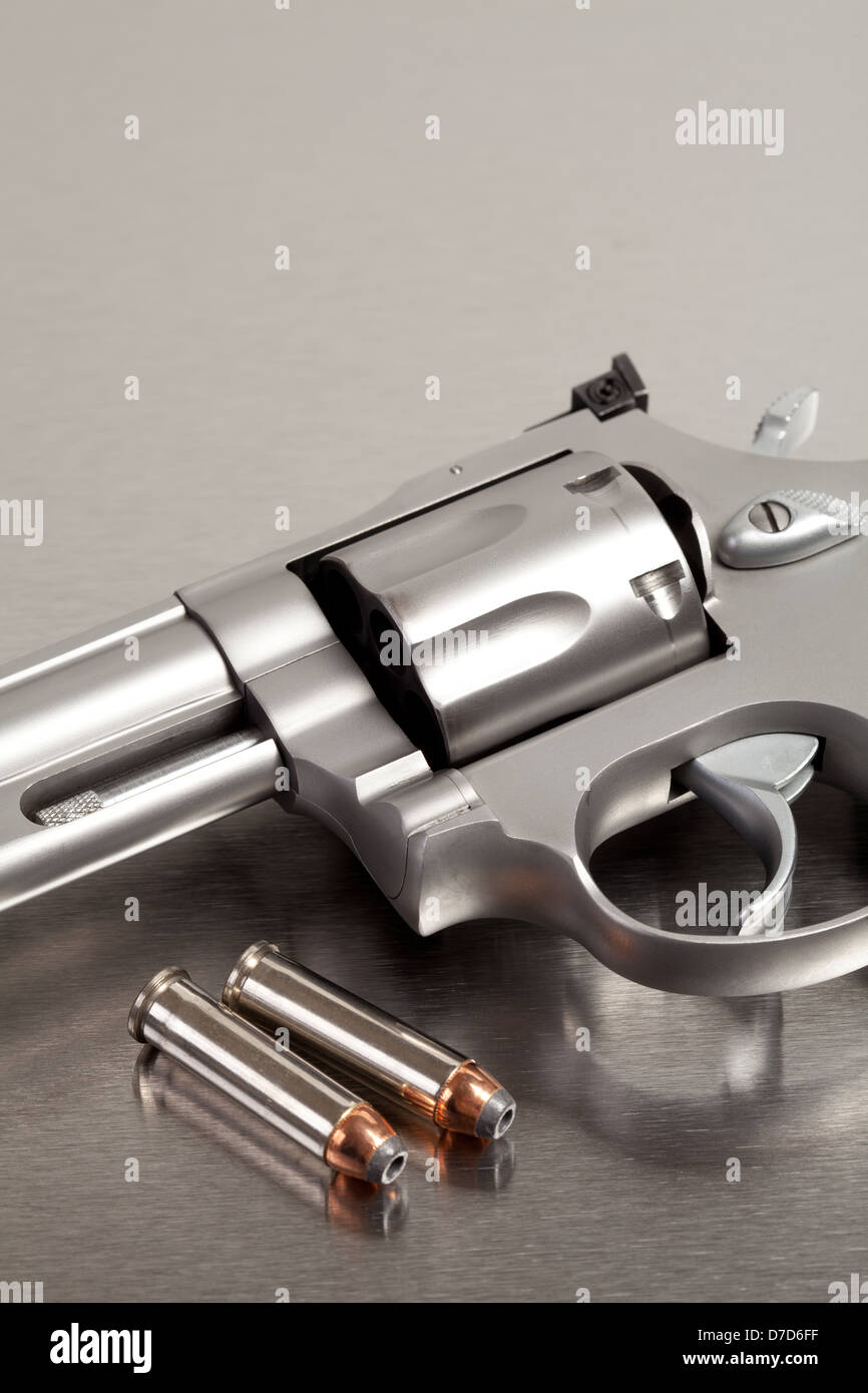Handgun with bullets - modern revolver on brushed metal with two bullets - Stock Image