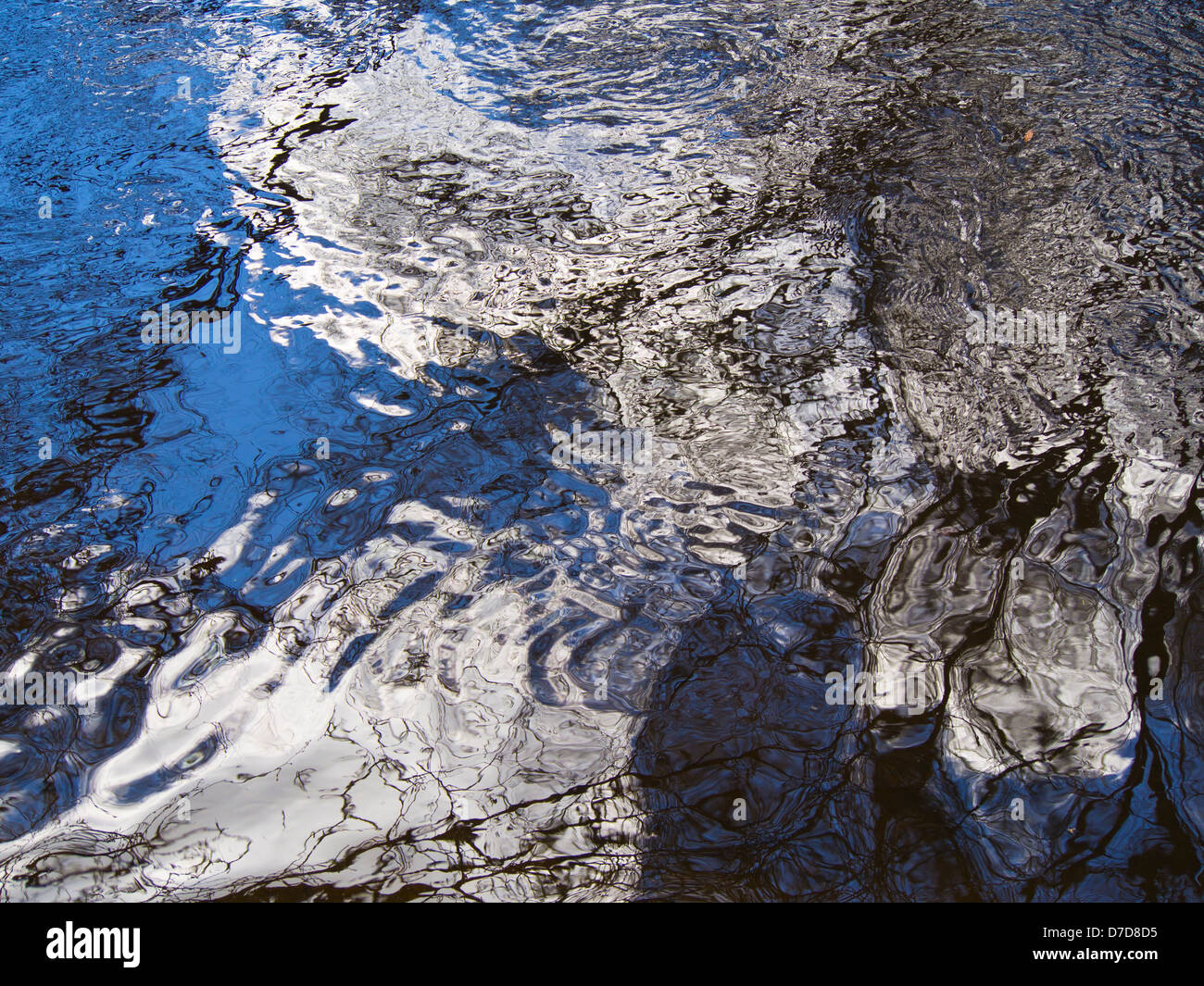 Blue white and black reflections in rippled water, abstract - Stock Image