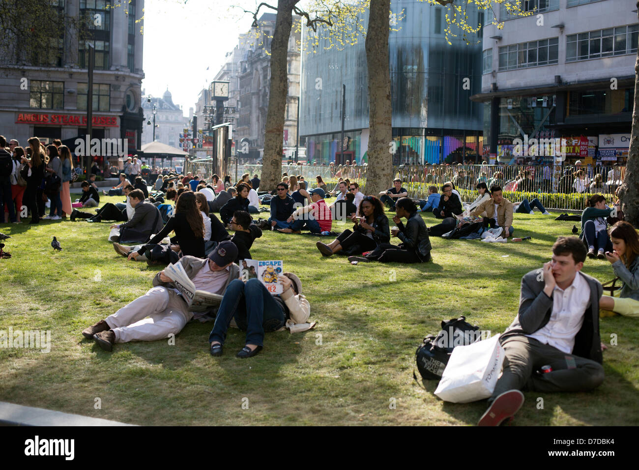 Leicester Square, London England people relaxing on grass - Stock Image