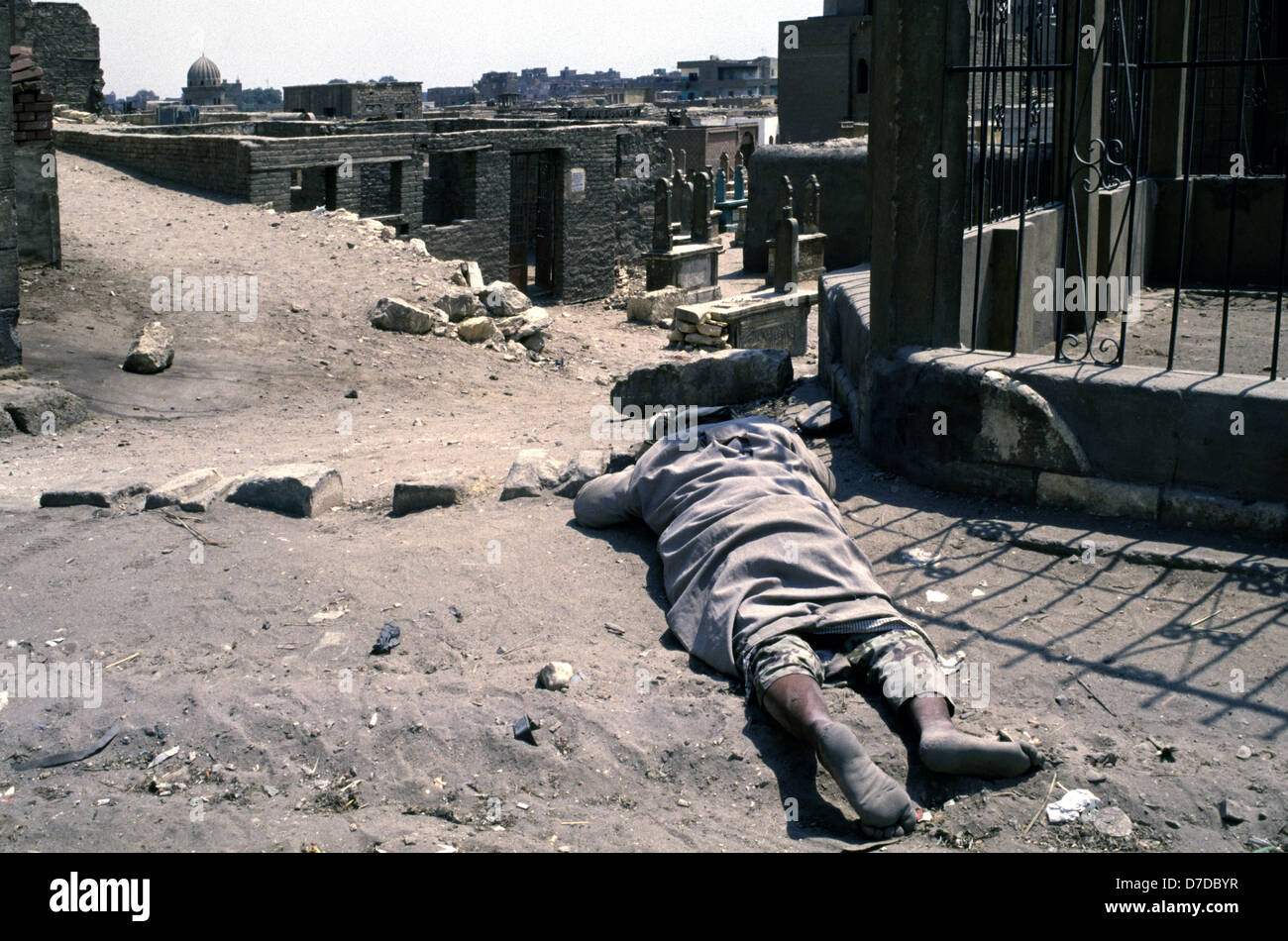 A homeless person sleeping in the ground amid dense grid of tomb and Islamic mausoleum structures in the City of - Stock Image
