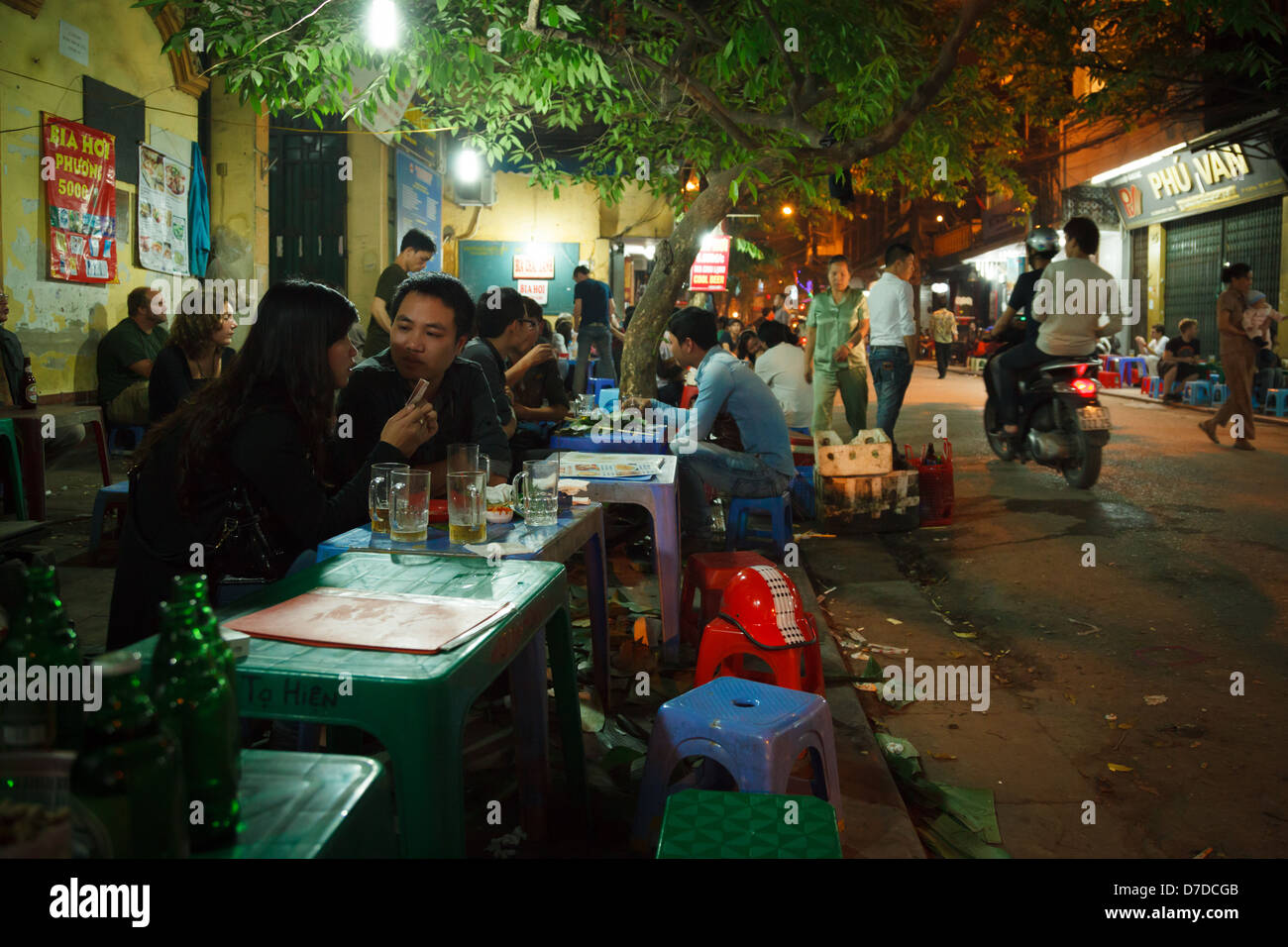 People enjoying bia hơi (Draught Beer) at a street outlet on the streets of the Old Quarter in Hanoi, Vietnam - Stock Image
