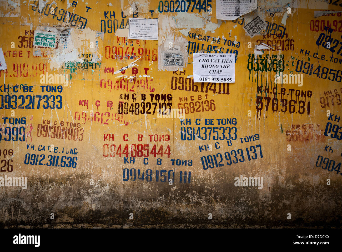 Adverts on a wall in a residential area of Hanoi, Vietnam - Stock Image