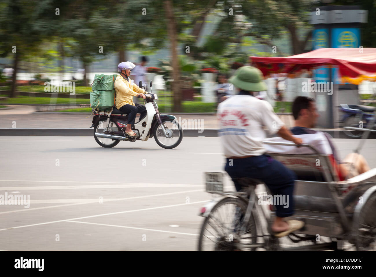 A man on his scooter driving past Hoam Kiem Lake and a Rickshaw in Hanoi, Vietnam - Stock Image