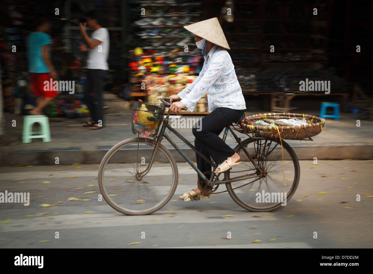 A street vendor on her bicycle in the Old Quarter of Hanoi, Vietnam - Stock Image