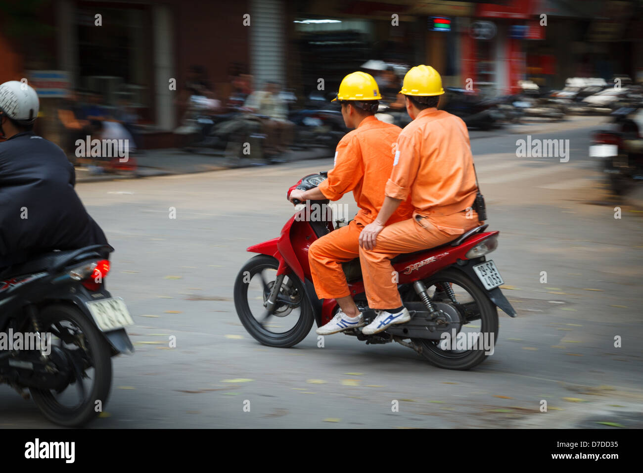 Two engineers (male) on a scooter in the Old Quarter, Hanoi. Stock Photo