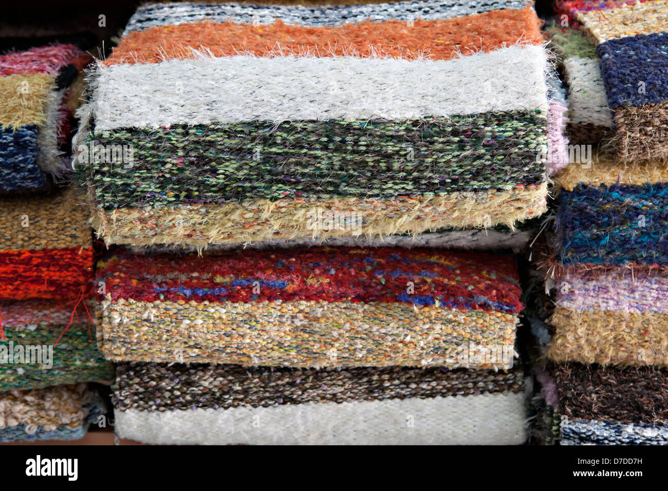 Large group of rugs on shelves - Stock Image