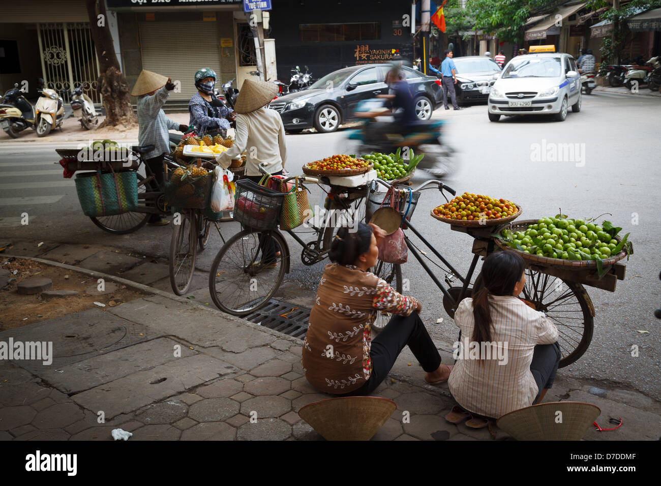 Street vendors selling their fruit from their bicycles in the Old Quarter of Hanoi, Vietnam - Stock Image