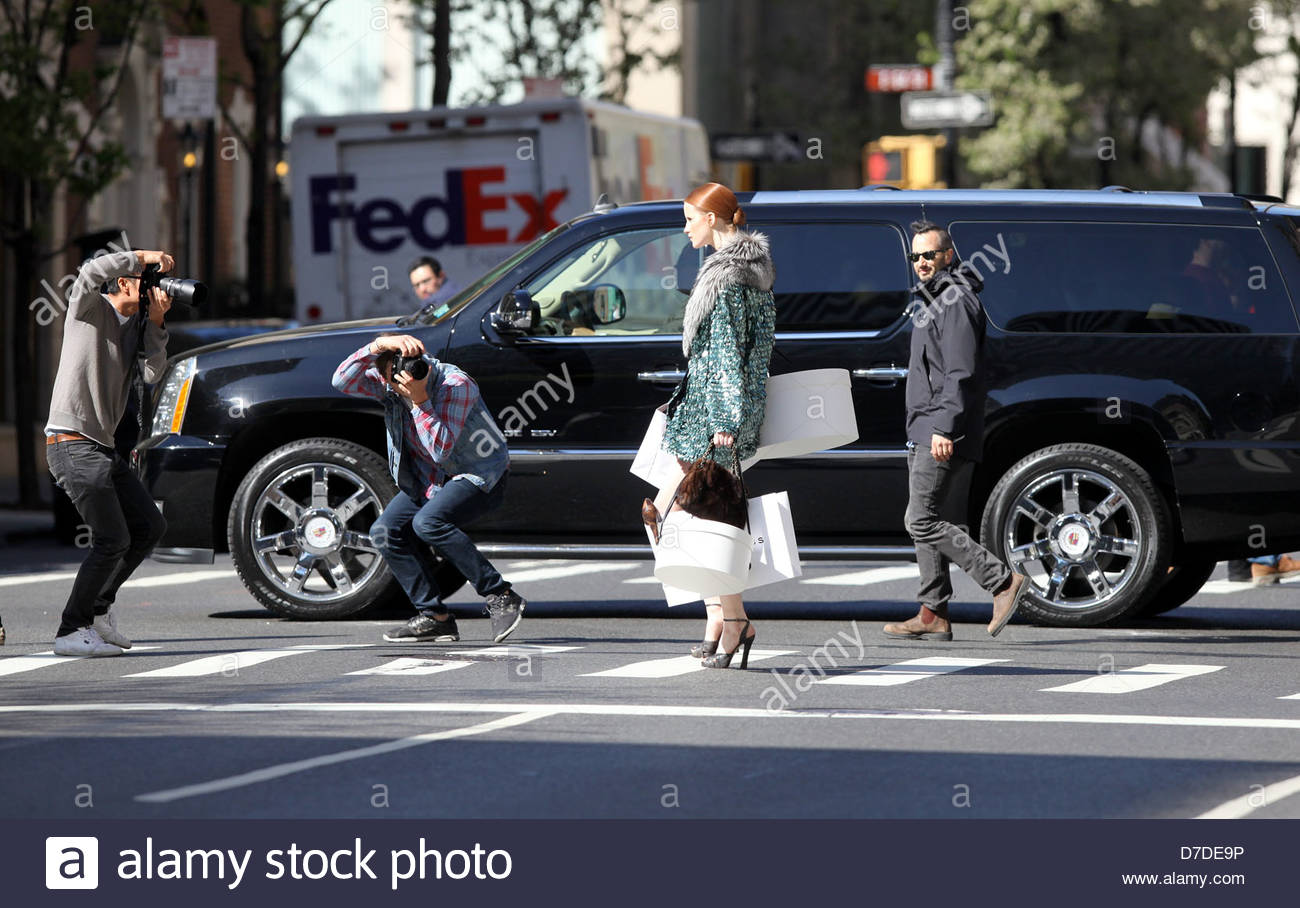 A model carries shopping bags during a photo shoot on Madison Avenue in Manhattan, New York, USA - Stock Image