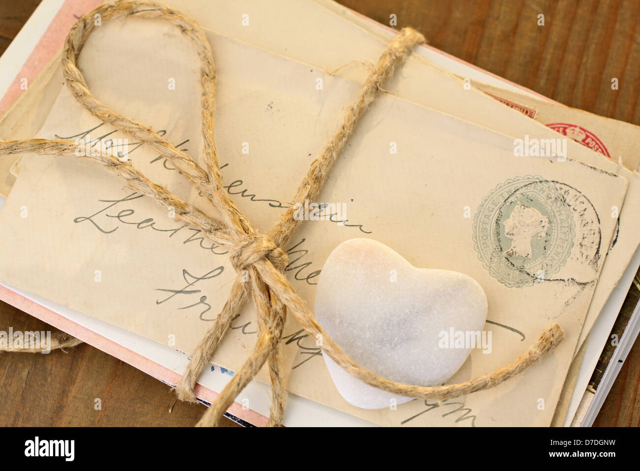 Stone heart with old tied letters on wooden desk - Stock Image