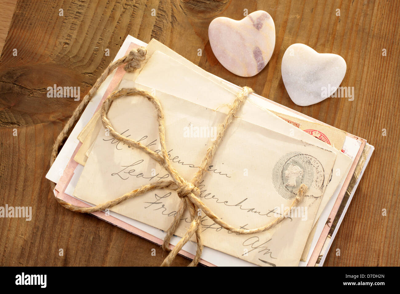 Stone hearts with old tied letters on wooden desk - Stock Image