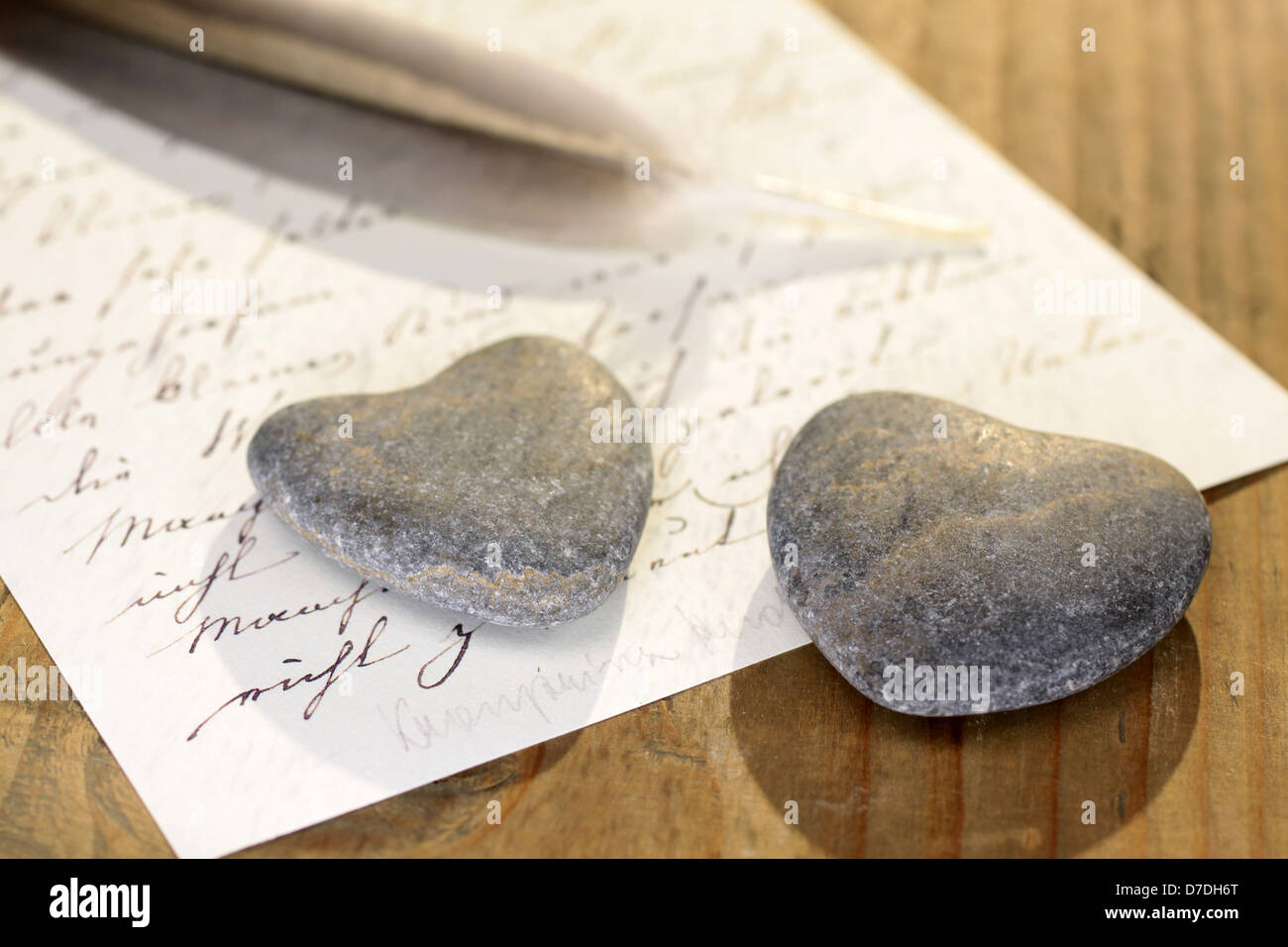 Two stone hearts with feather and old letter - Stock Image