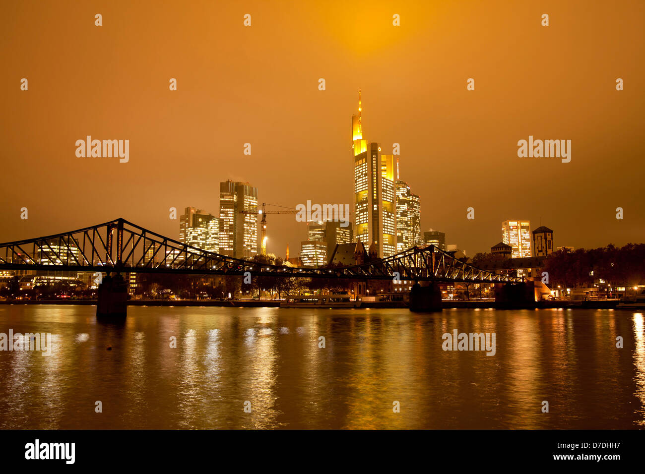Eiserner Steg Bruecke, bridge over the Main river with the illuminated skyline of Frankfurt at dusk, Frankfurt am - Stock Image