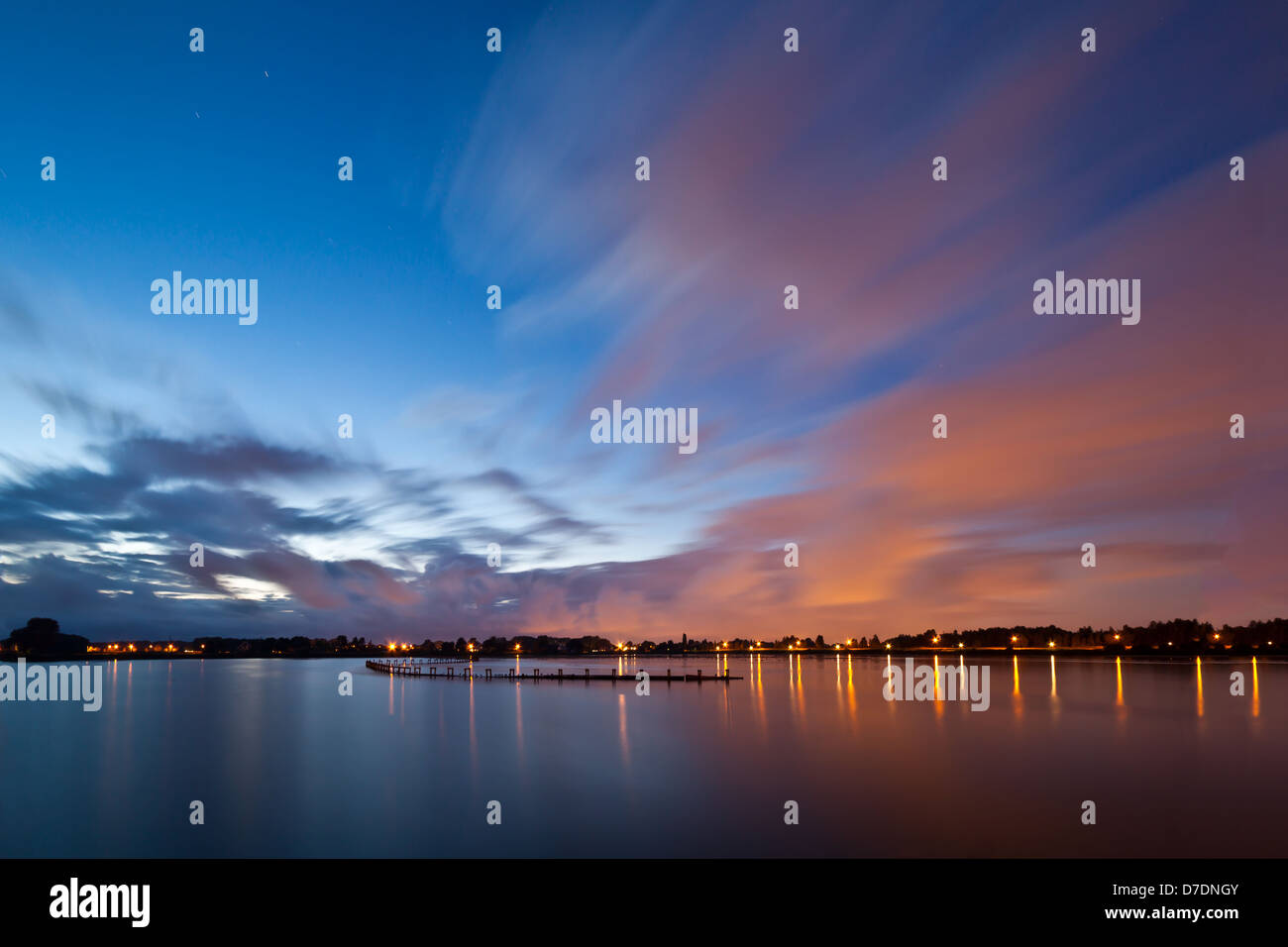 Impressive clouds above a blue lake at night - Stock Image