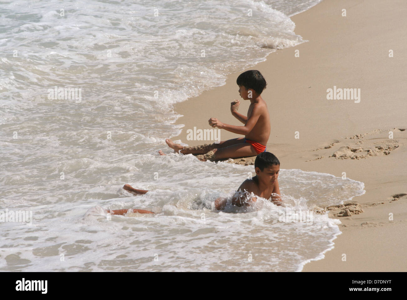 Two boys have fun with the rolling waves at Leme Beach, on a sunny autumn day. Rio de Janeiro, Brazil - Stock Image