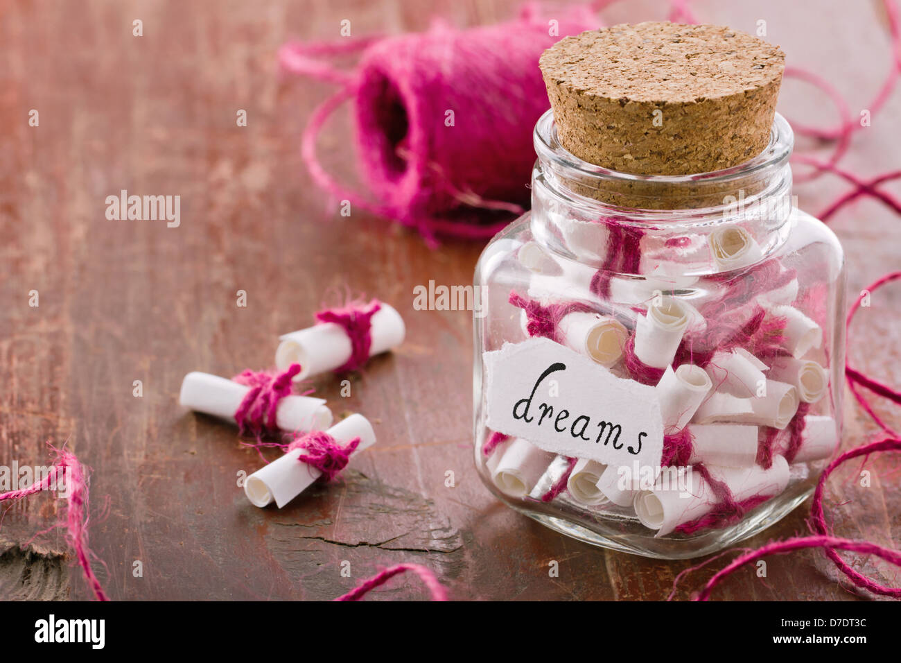 Dreams written on a white rolled paper in a glass jar on rustic vintage wooden background, dreaming optimism concept - Stock Image