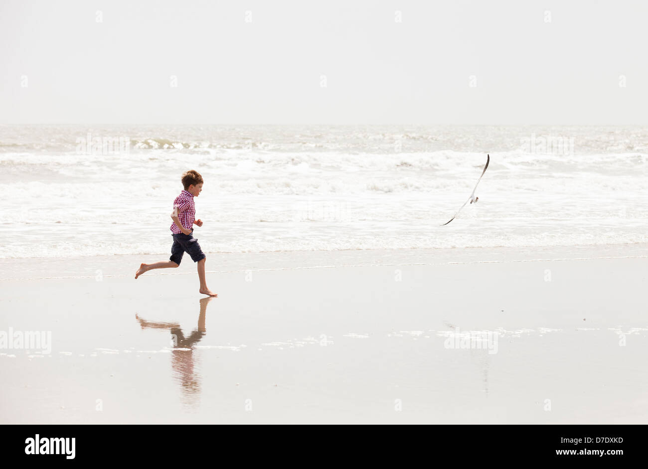boy running on beach - Stock Image