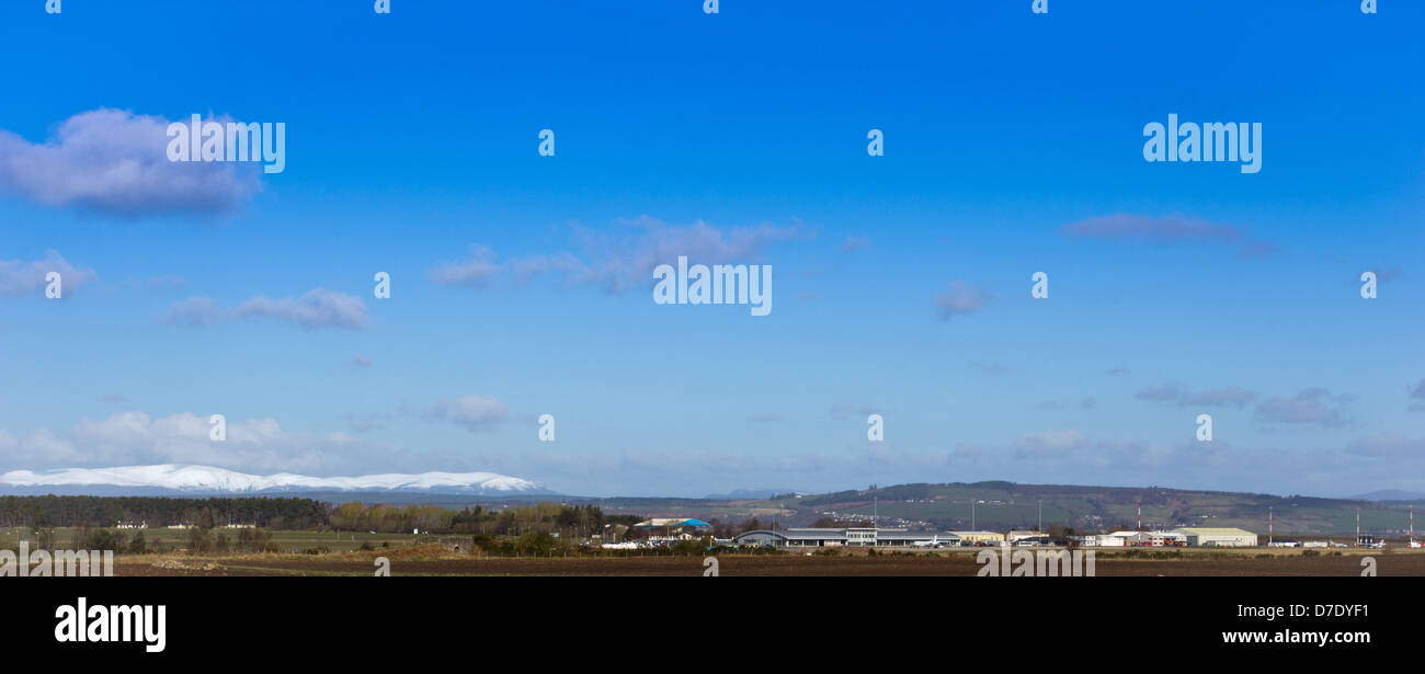 INVERNESS DALCROSS AIRPORT ON A SPRING MORNING IN APRIL WITH SNOW ON THE BEN WYVIS MOUNTAIN RANGE IN THE DISTANCE - Stock Image