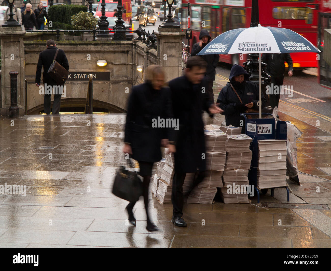 Captured with motion blur a couple hurry past a Evening Standard newspaper stand outside Bank station London. - Stock Image