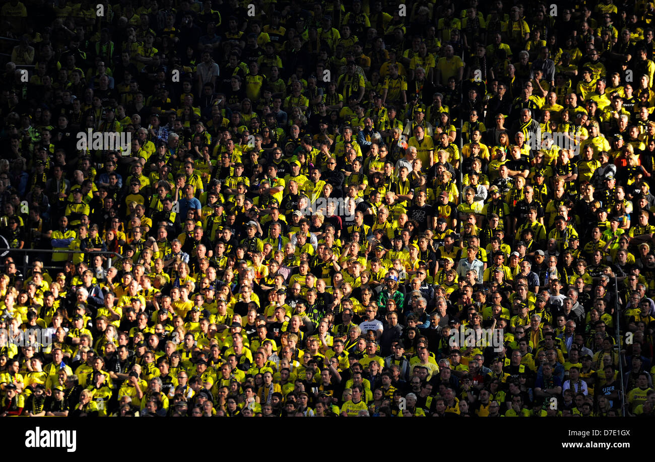 Fans of football club Borussia Dortmund form a pattern of the clubs colors in black and yellow in the stands - Stock Image