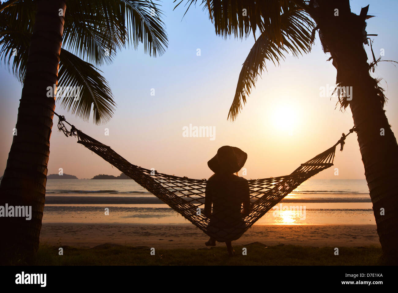 silhouette of woman in hat sitting in hammock at sunset on the beach - Stock Image