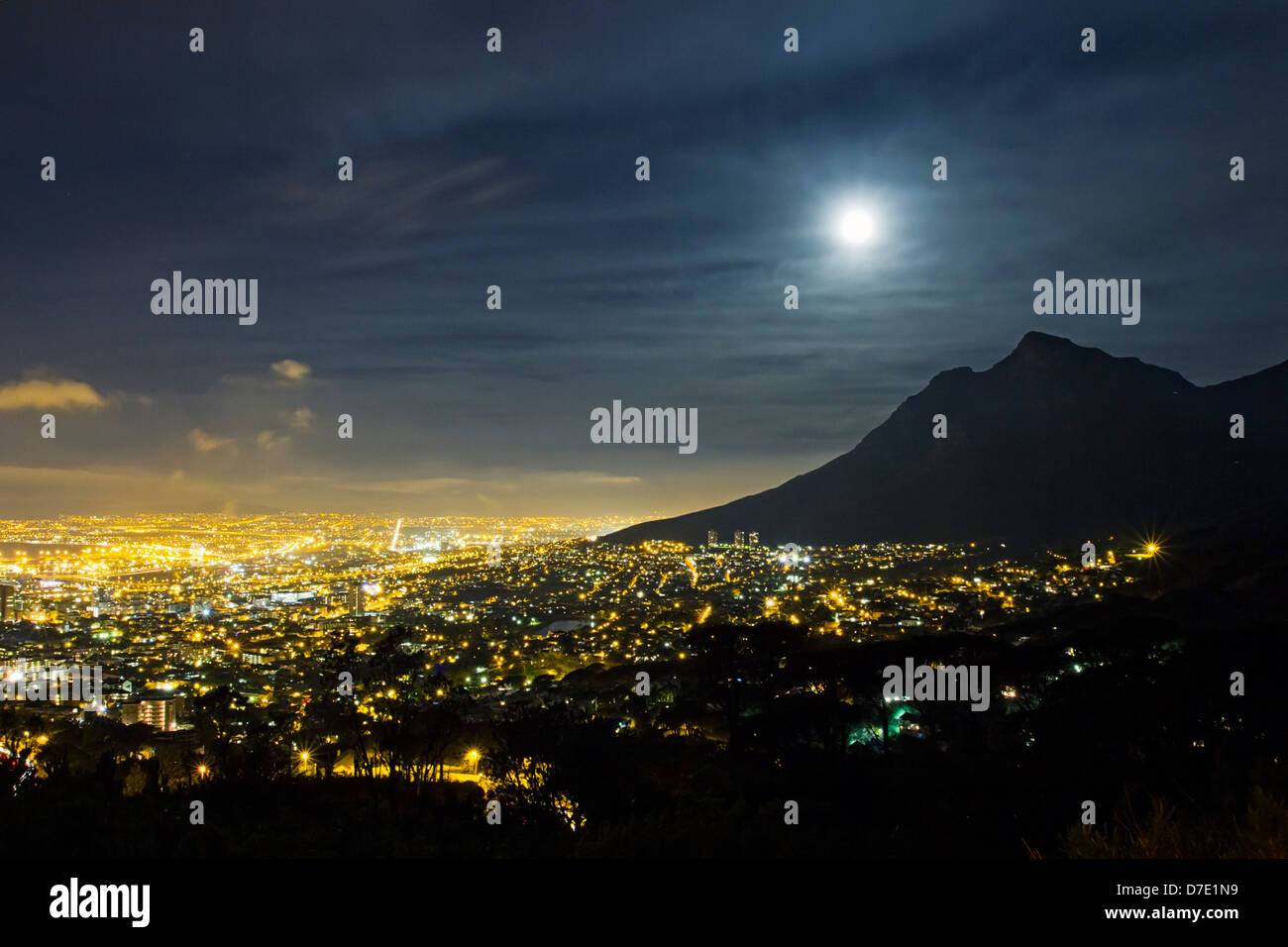 Lights of Cape Town city and full moon over Devils Peak, Table Mountain at night - Stock Image