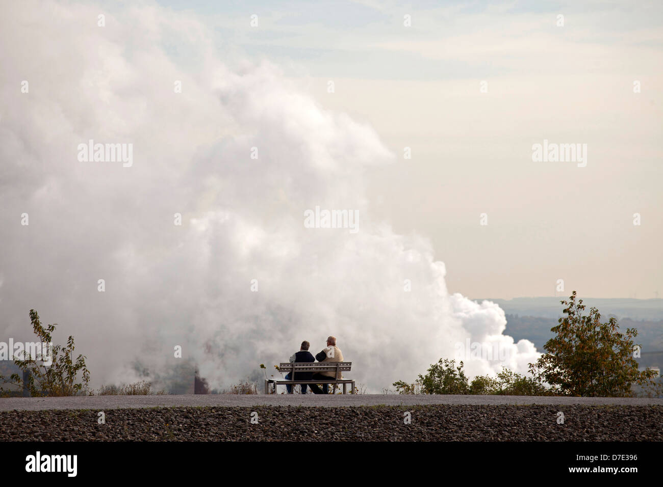 Couple on a bench in front of air pollution from a power plant in Bottrop, Ruhr Area, North Rhine-Westphalia, Germany, - Stock Image