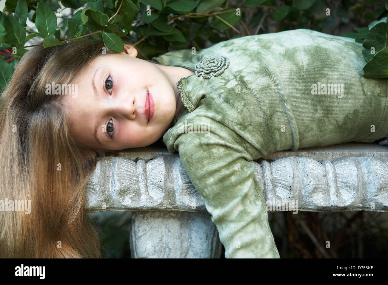 7 year old girl lying on garden bench - Stock Image