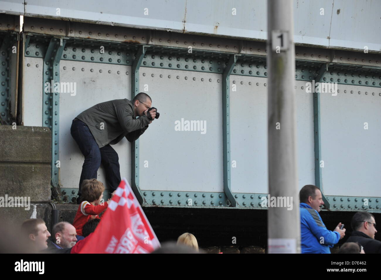 CARDIFF, UK. 5th May 2013. A fan climbs onto a bridge to photograph the Cardiff City Champions Parade.The team were - Stock Image