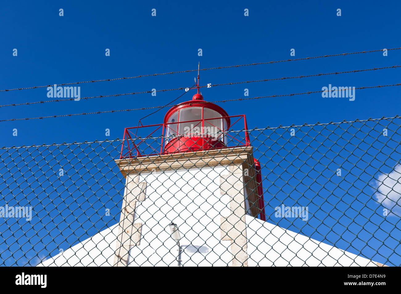 Bright Lighthouse beyond chain link fence against Blue Sky Background - Stock Image