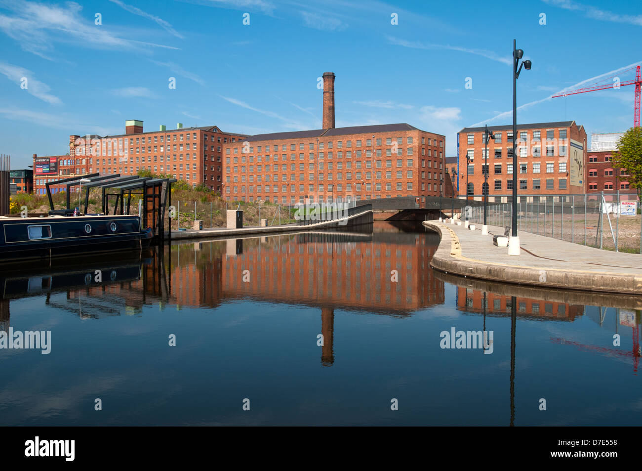 Former cotton mills, now apartments, reflected in the Cotton Field Park marina, New Islington, Ancoats, Manchester, - Stock Image