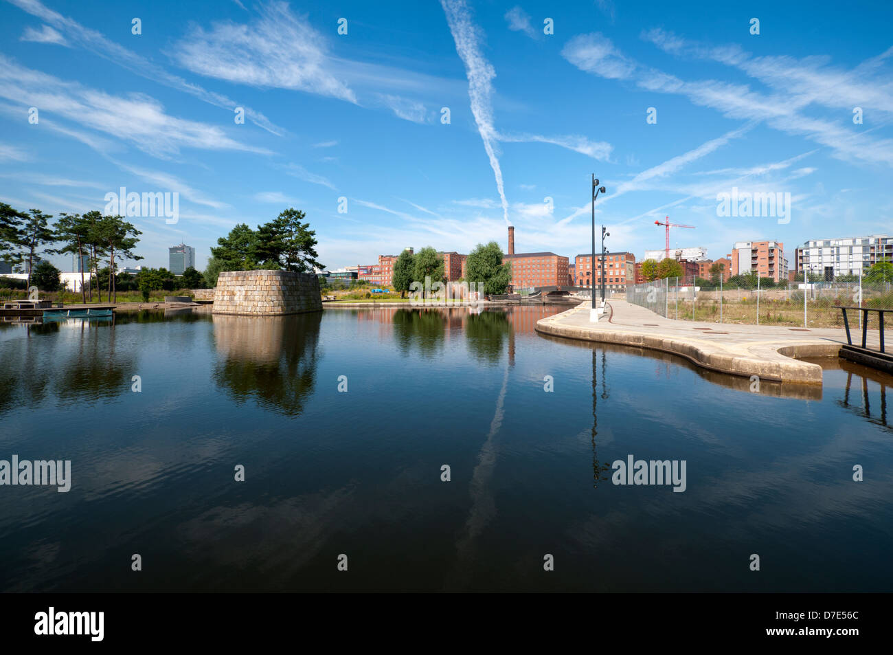 Cirrus clouds and former cotton mills reflected in the Cotton Field Park marina, New Islington, Ancoats, Manchester, - Stock Image
