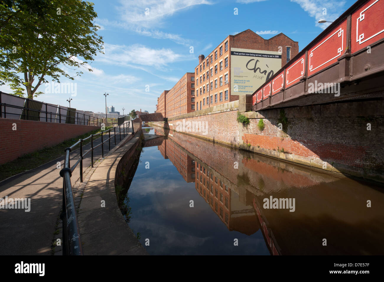 Road bridge and former cotton mills reflected in the Rochdale Canal, New Islington, Ancoats, Manchester, England, - Stock Image