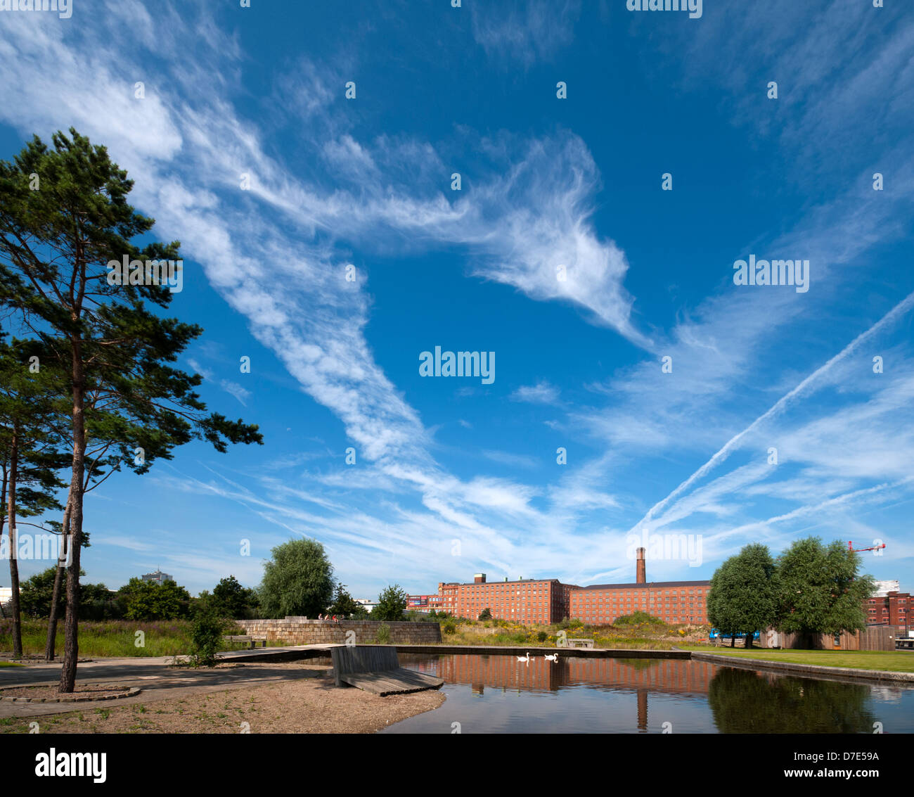 Cirrus clouds and former cotton mills reflected in the Cotton Field Park marina, New Islington, Ancoats, Manchester, Stock Photo