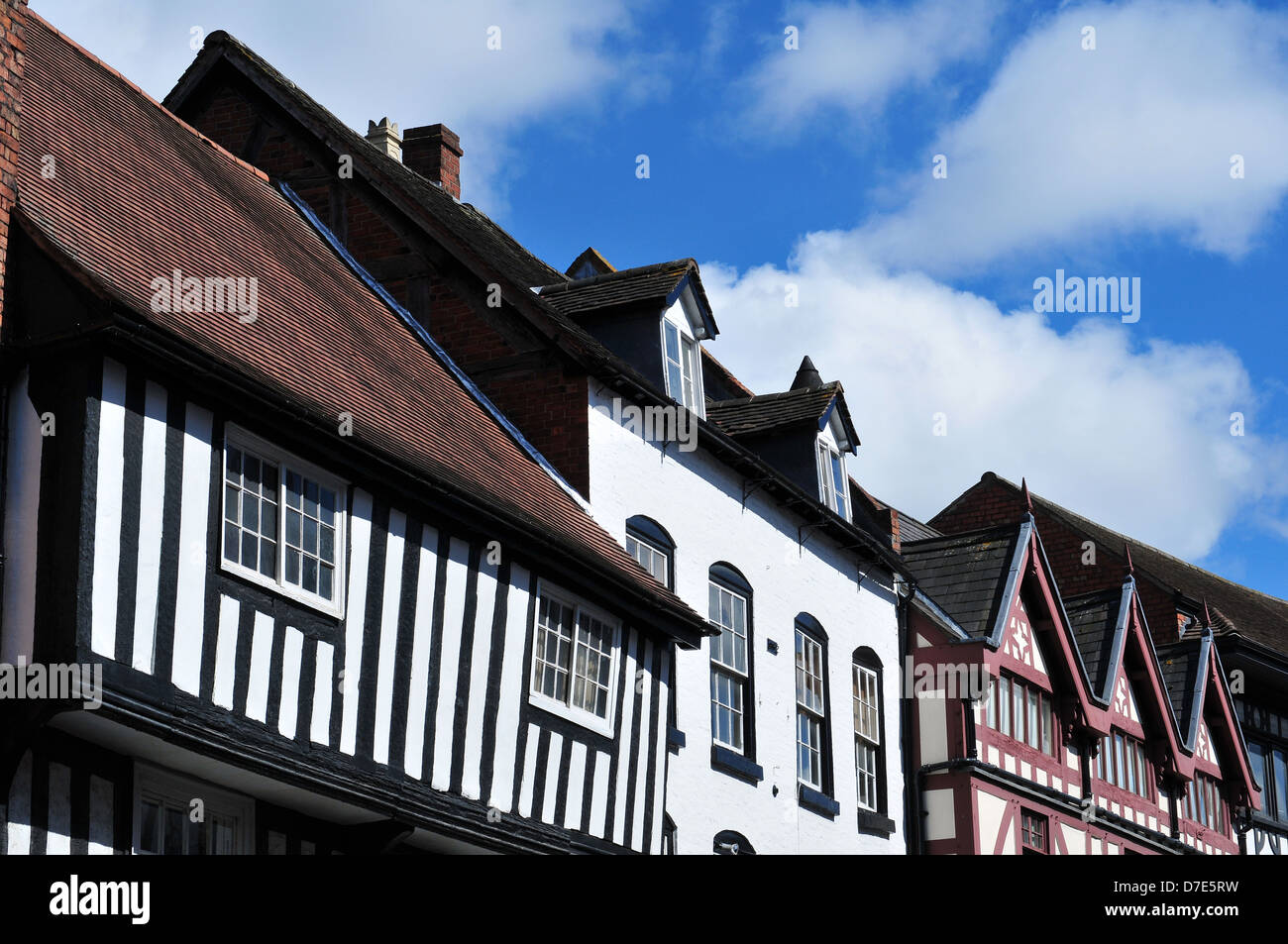 Mixed roof line of historic houses in Mardol, Shrewsbury, UK. Half-timbered buildings and brick properties stand - Stock Image