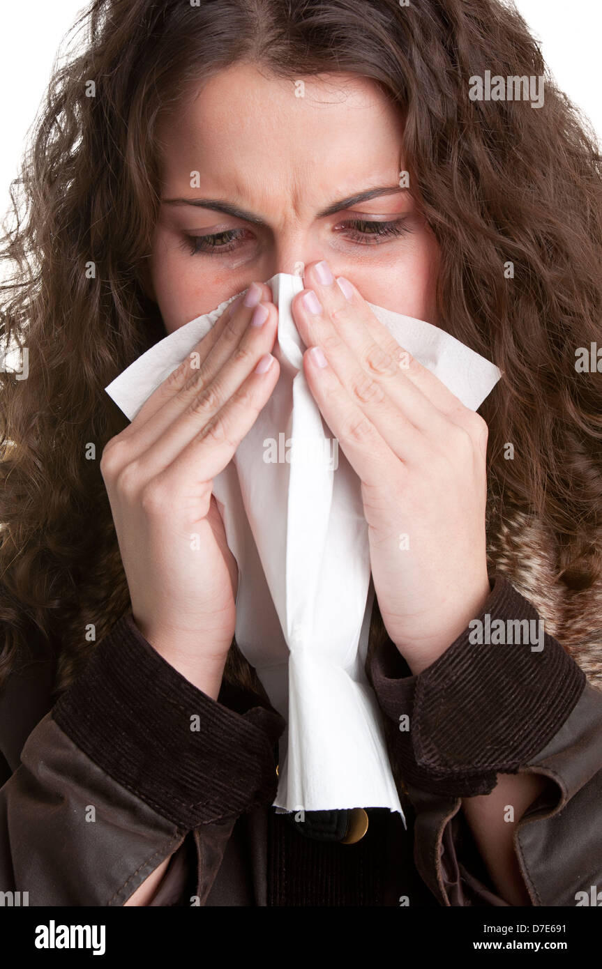 Pale sick woman with a flu, sneezing, in a white background - Stock Image