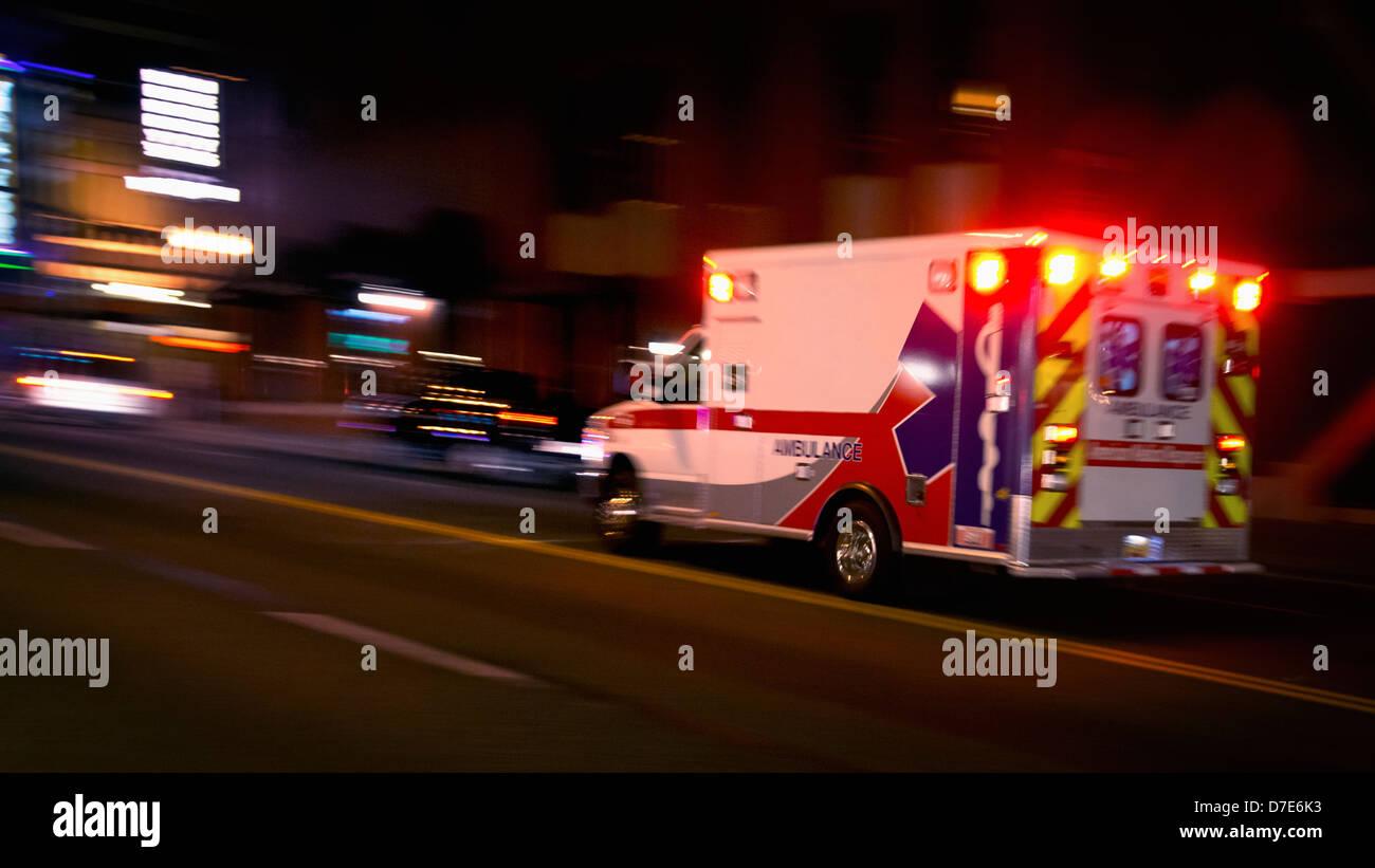 An ambulance speeding through traffic at nighttime - Stock Image
