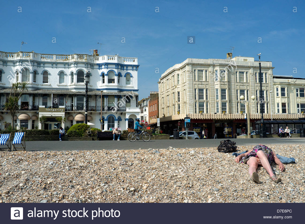A sunbather lies on the beach on Worthing seafront. West Sussex, UK. - Stock Image