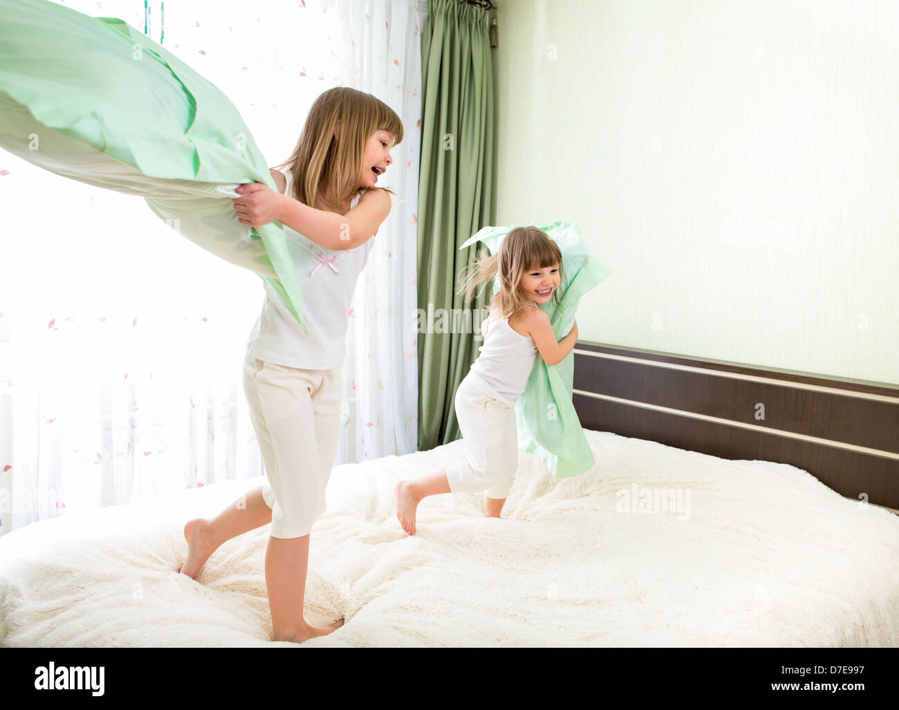 Little girls fighting using pillows in bedroom - Stock Image