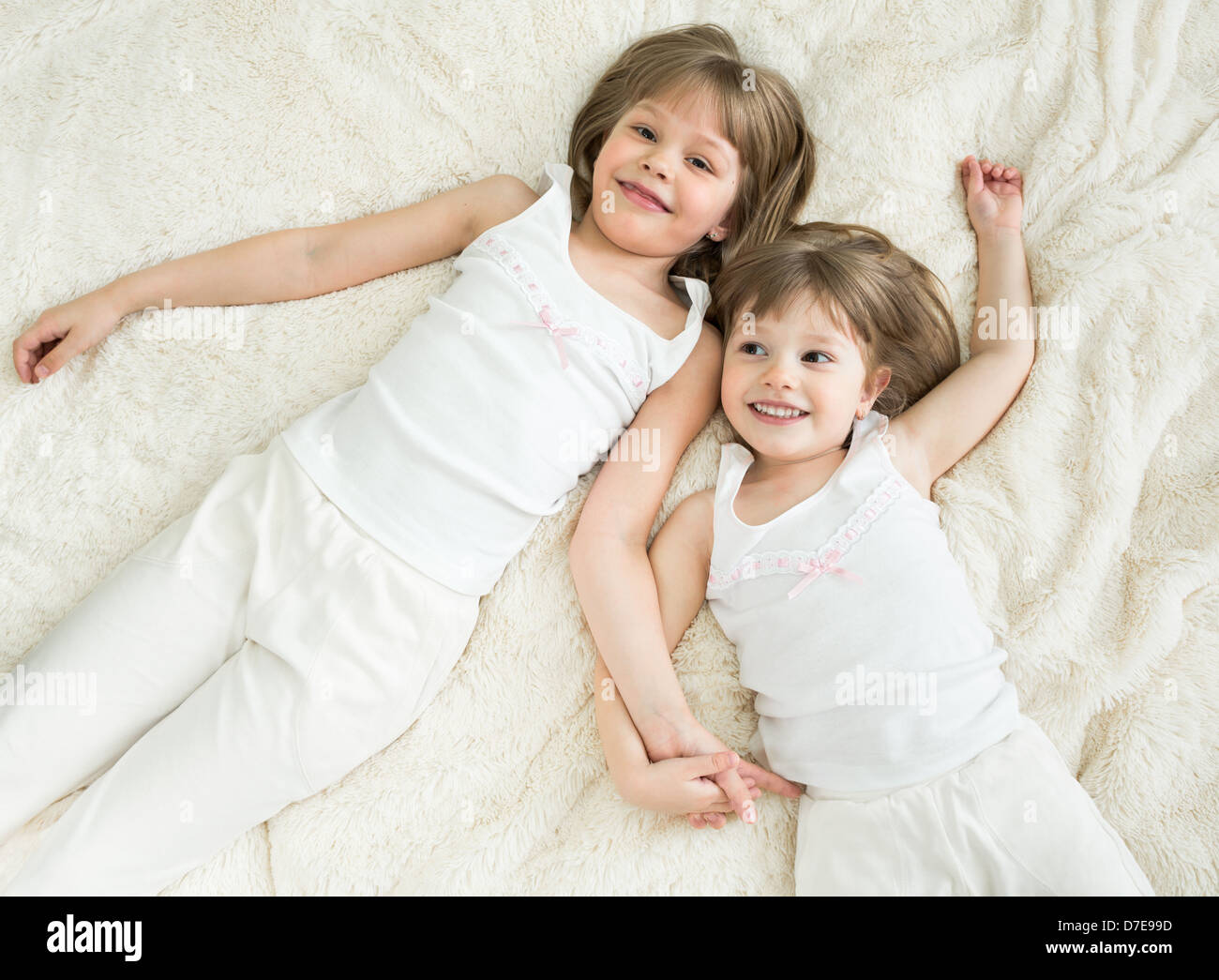 happy little sisters lying on back top view - Stock Image