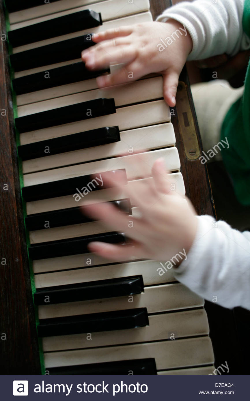 High angle view of a child playing a piano - Stock Image