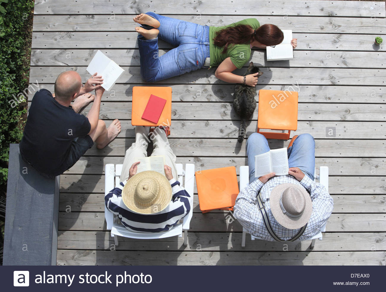High angle view of a family reading novels on the boardwalk, Bonn, Germany - Stock Image
