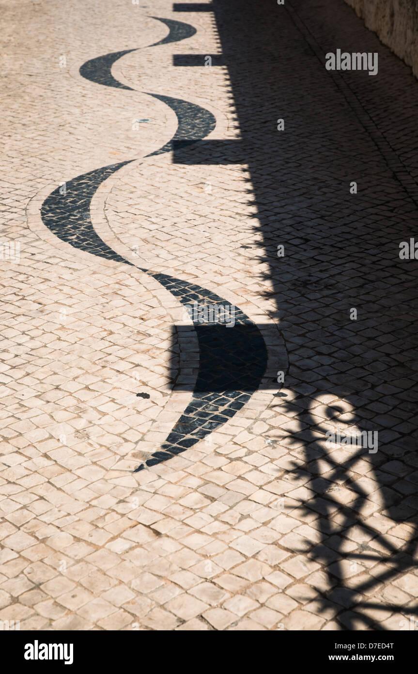 Overlap between cobblestone and shadow - Stock Image