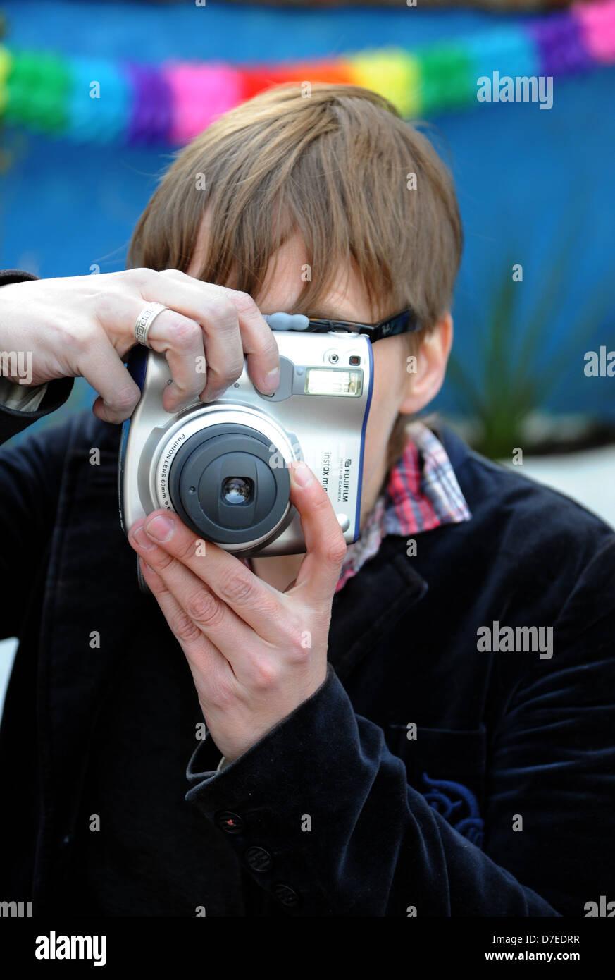 Woman using a Fuji Fujifilm instax 210 film instant camera Photograph taken by Simon Dack - Stock Image
